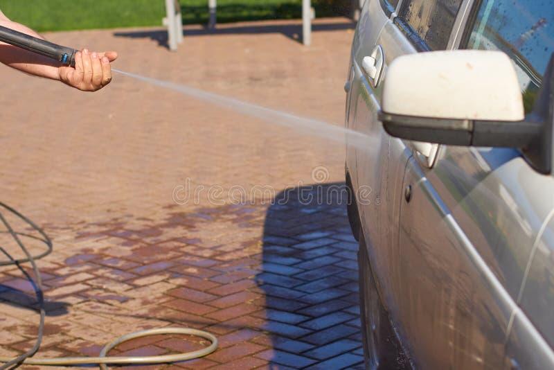Myć białego brudnego samochód z wodnym strumieniem od płuczkowego machina fotografia stock