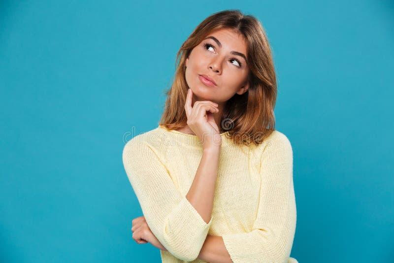 Myśląca ładna kobieta nad błękitnym tłem zdjęcia royalty free