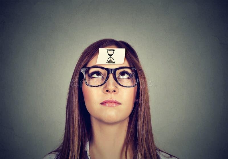 Myśląca kobieta z piaska zegaru majcherem na czole Czasu zarządzania pojęcie obrazy stock