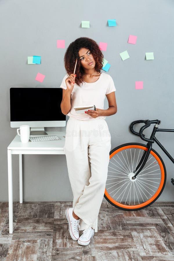 Myśląca młoda afrykańska kobieta stoi blisko komputeru obrazy royalty free