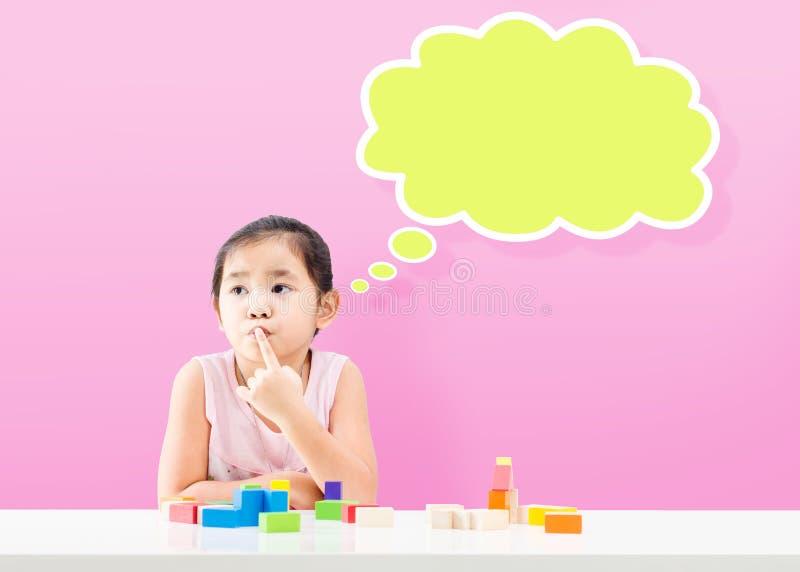 Myśląca mała dziewczynka z pustym bąblem i drewnianym elementem fotografia stock
