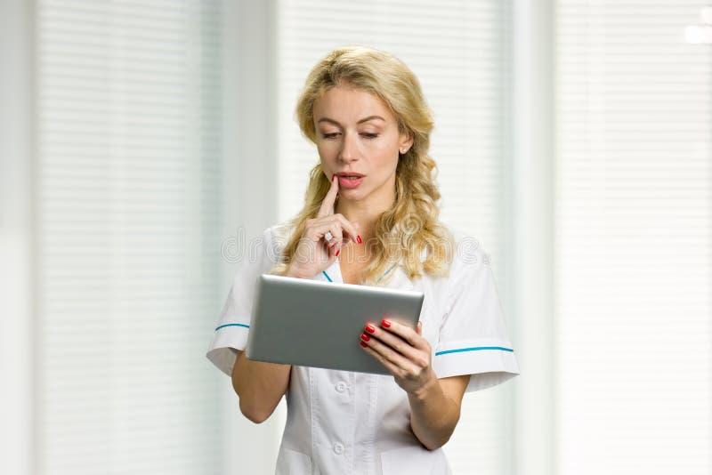 Myśląca pielęgniarka używa cyfrową pastylkę obraz royalty free
