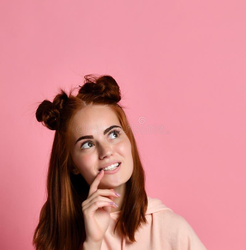 Myśląca rudzielec młoda kobieta w hoodie przyglądającym w górę zdjęcia royalty free