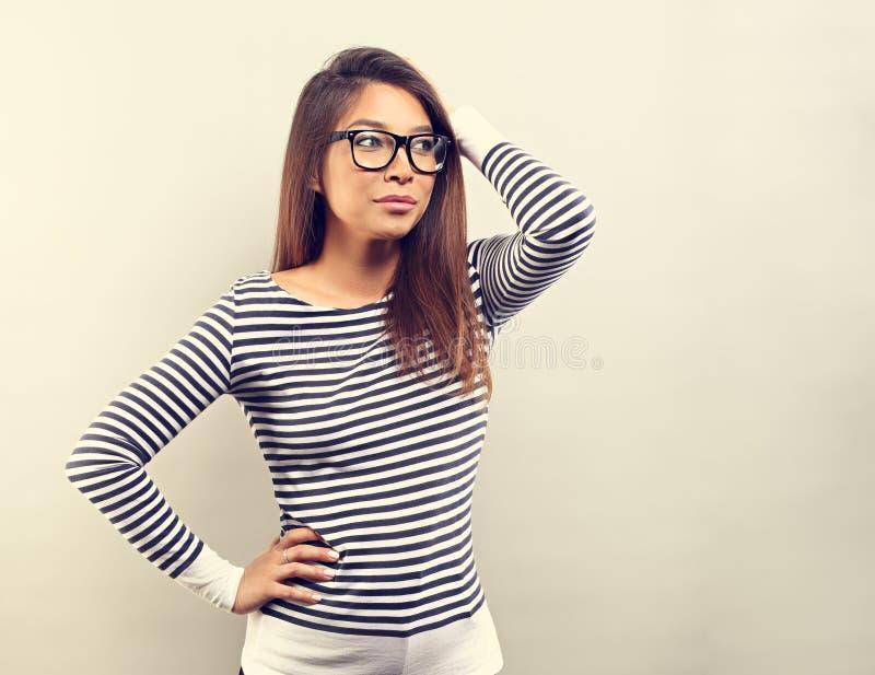 Myśląca skeptic Latina młoda kobieta w eyeglasses myśleć i s zdjęcia royalty free