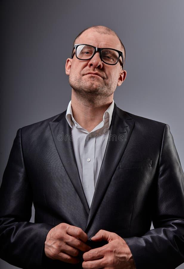 Myślącej zabawy łysy biznesowy mężczyzna patrzeje poważny w eyeglasses w kostiumu na popielatym tle zbli?enie fotografia stock
