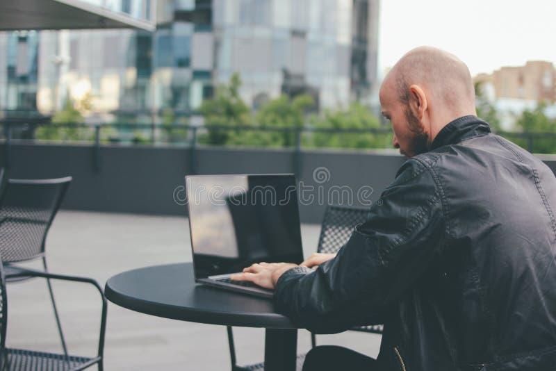Myślący atrakcyjny dorosły pomyślny łysy brodaty mężczyzna w czarnej kurtce z laptopem w ulicznej kawiarni przy miastem fotografia stock