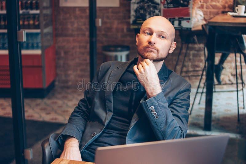 Myślący atrakcyjny dorosły pomyślny łysy brodaty mężczyzna w kostiumu z laptopem w kawiarni obraz royalty free