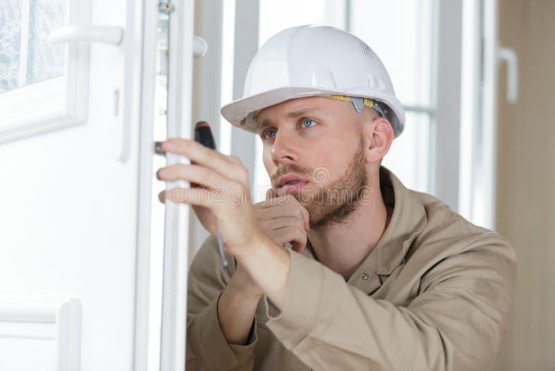 Myślący budowniczy przed śrubować ścianę fotografia stock