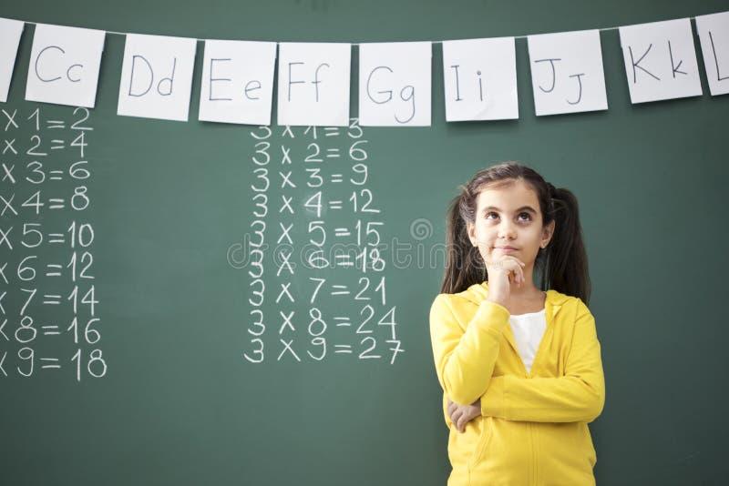 Myślący dziecko w wieku szkolnym blisko blackboard zdjęcia stock