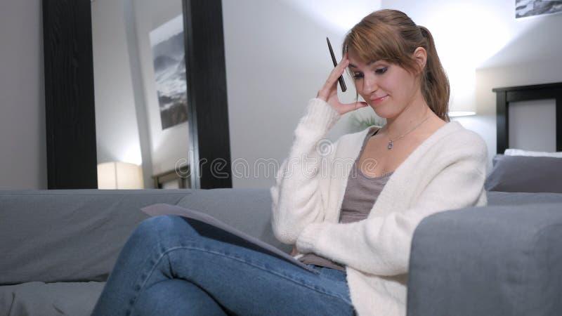 Myślący kobiety czytania dokumenty, Siedzi na kanapie fotografia royalty free