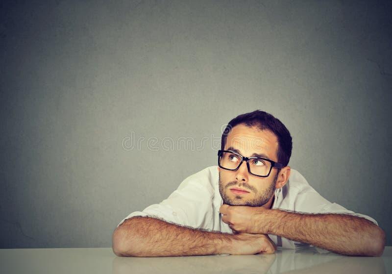 Myślący młody biznesowego mężczyzna obsiadanie przy stołem fotografia royalty free