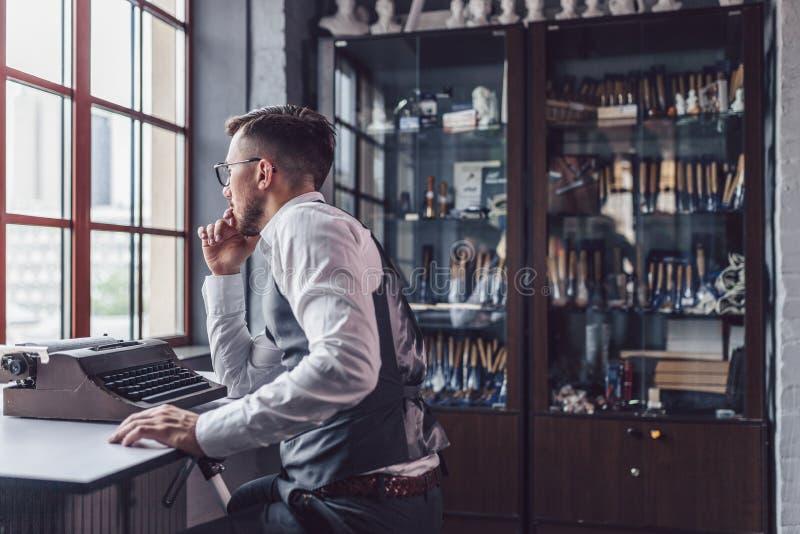 Myślący młody człowiek przy biurkiem fotografia royalty free