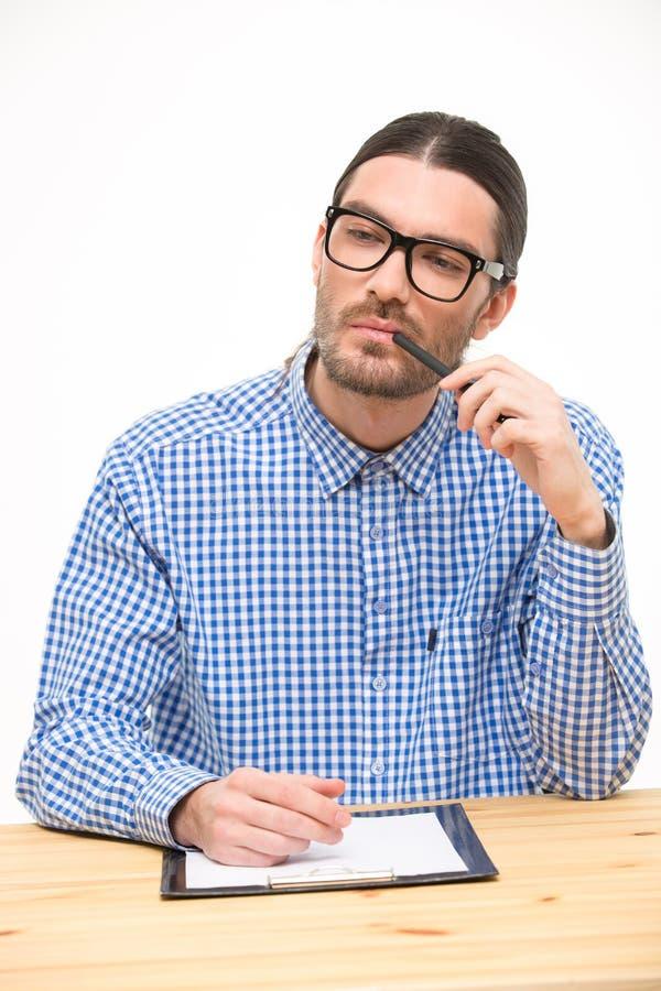 Myślący młody człowiek siedzi przy biurkiem w szkłach obrazy stock