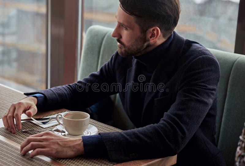 Myślący przystojny mężczyzny obsiadanie w kawiarni i pić filiżanka kawy na śniadaniowym zbliżenie portrecie fotografia stock