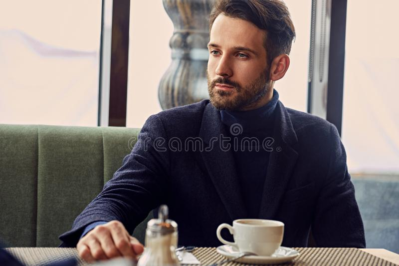 MyÅ›lÄ…cy przystojny mężczyzny obsiadanie w kawiarni i pić filiżanka kawy na Å›niadaniowym zbliżenie portrecie zdjęcia stock