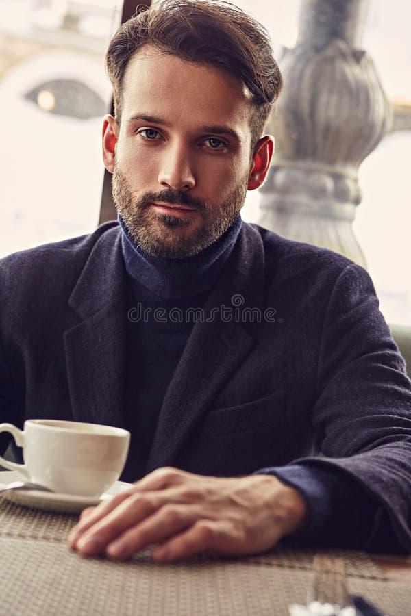MyÅ›lÄ…cy przystojny mężczyzny obsiadanie w kawiarni i pić filiżanka kawy na Å›niadaniowym zbliżeniu zdjęcia stock