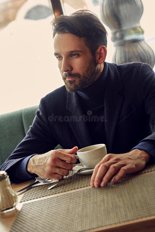 MyÅ›lÄ…cy przystojny mężczyzny obsiadanie w kawiarni i pić filiżanka kawy na Å›niadaniowym zbliżeniu zdjęcie stock
