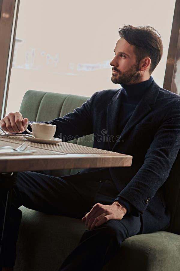 Myślący przystojny mężczyzny obsiadanie w kawiarni i pić filiżanka kawy na śniadaniowym zbliżeniu obrazy stock