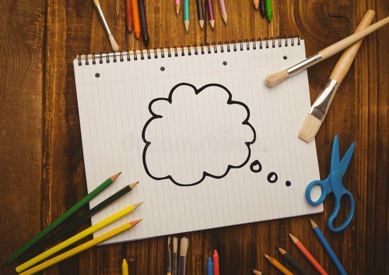 Myśl bąbel rysujący na notatniku umieszczającym z kolorystyk narzędziami obrazy royalty free