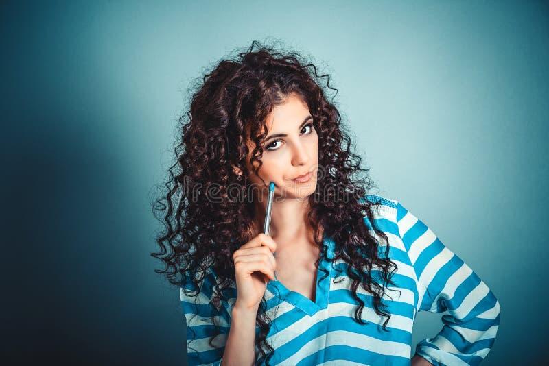 Myśleć kobieta patrzeje ciebie skeptically z kędzierzawego włosy mienia myślącym piórem na policzku obrazy royalty free