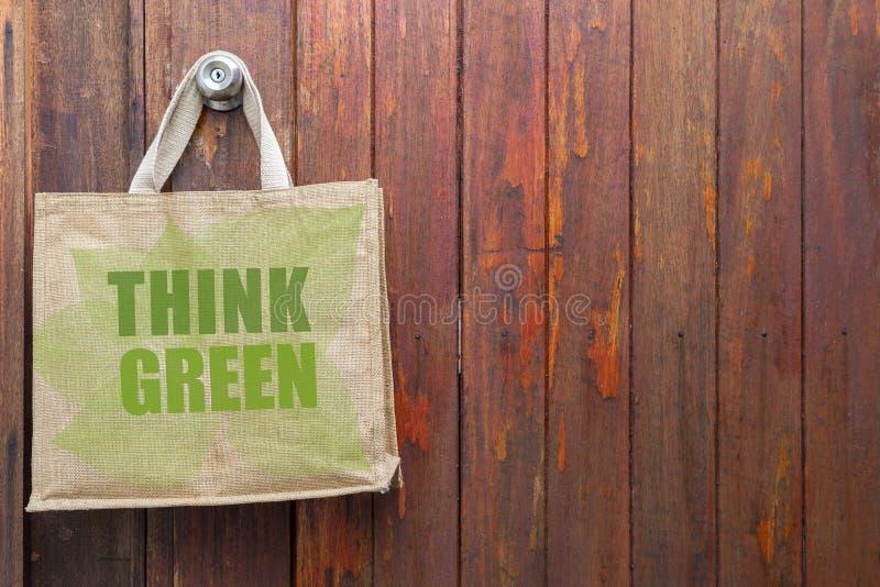 Myśleć Zielonego loga na jutowym sklep spożywczy torby obwieszeniu na starym drewnianym drzwi fotografia stock