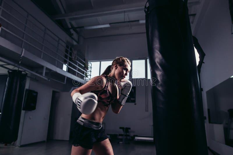 Myśliwska dziewczyna jest ubranym sportswear uderza pięścią torbę zdjęcie royalty free