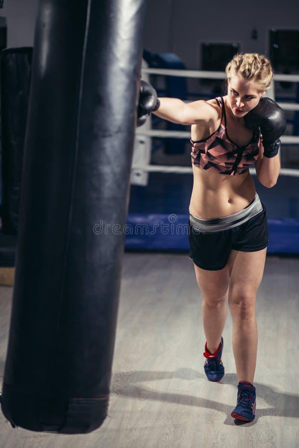 Myśliwska dziewczyna jest ubranym sportswear uderza pięścią torbę fotografia royalty free