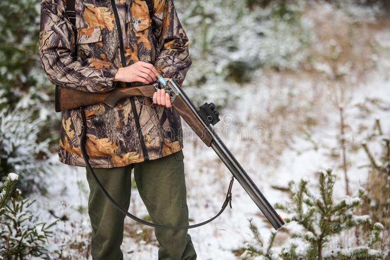 Myśliwy z plecakiem i łowieckim pistoletem w zima lesie zdjęcia royalty free