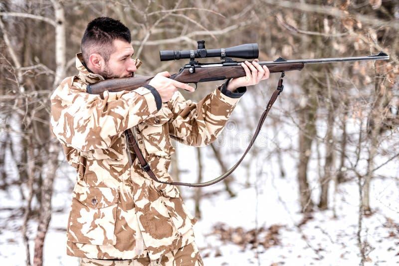 Myśliwy z snajperskim celowaniem podczas zima łowieckiego sezonu i strzelanina w lesie obraz royalty free