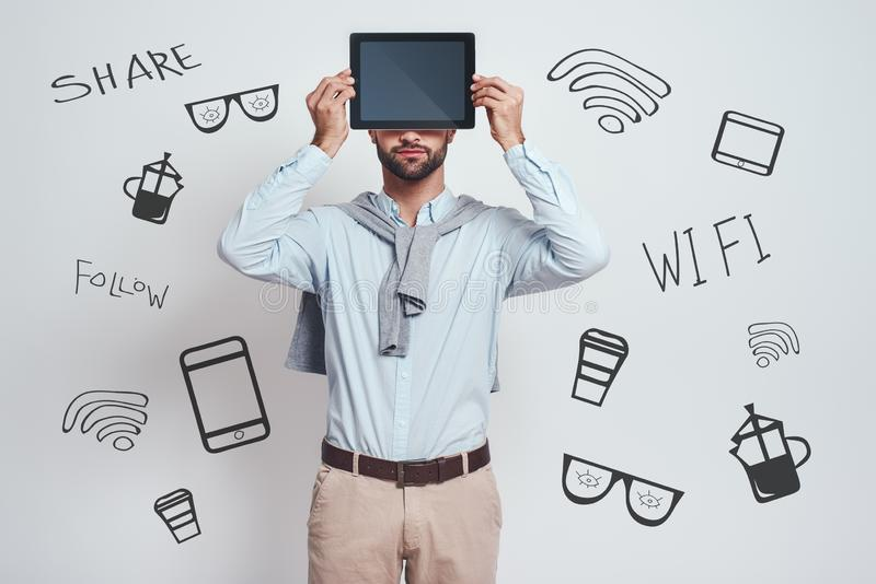 My assistant in any cases. Bearded man in casual clothes is holding his digital tablet in front of his head while stock image