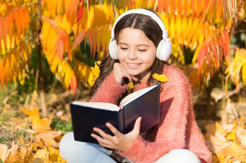 My autumn story. Little child listen to ebook in headphones. Little child enjoy learning in autumn park. Ebook holds stock photos