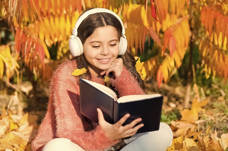 My autumn story. Little child listen to ebook in headphones. Little child enjoy learning in autumn park. Ebook holds royalty free stock photography