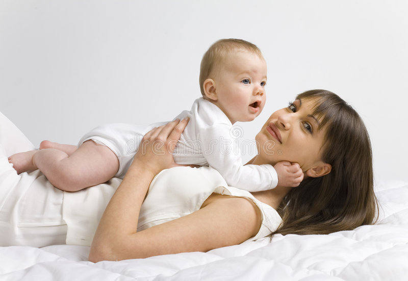 My baby. Young mother with baby boy. Lying on bed and hugging. Looking at camera, side view