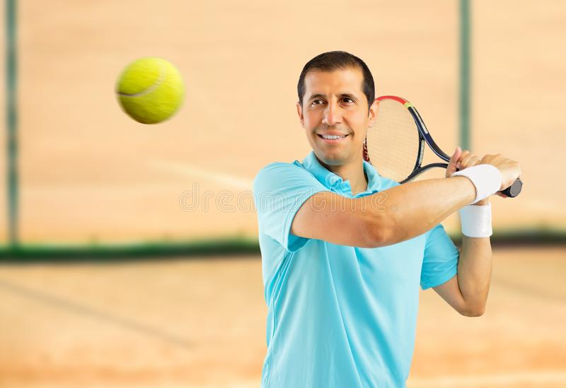 This is my ball. Portrait of a male tennis player swatting the ball on a clay court royalty free stock images