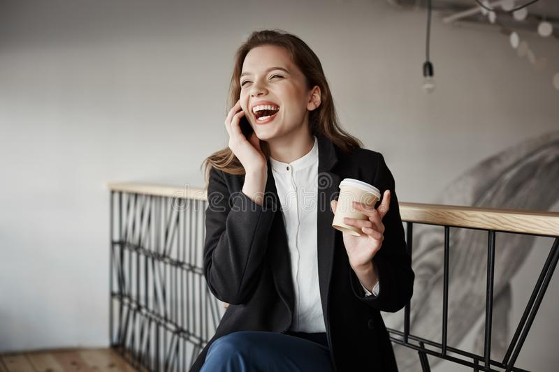 My belly hurts from laugh. Portrait of emotive good-looking caucasian girl in stylish clothes sitting in coffee shop. Drinking cup of tea, speaking via stock photos