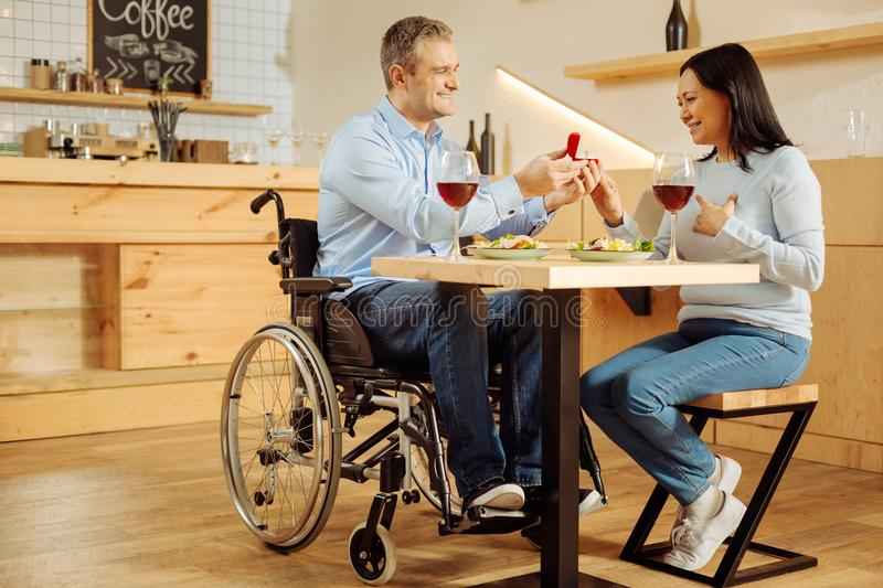 Happy disabled man proposing to his beloved woman. My beloved. Good-looking joyful handicapped men smiling and proposing to his pretty beloved inspired women and stock photos