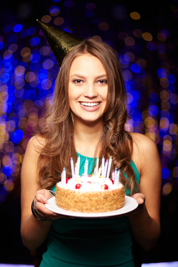 My birthday. Portrait of joyful girl holding birthday cake with candles and looking at camera at party stock photography