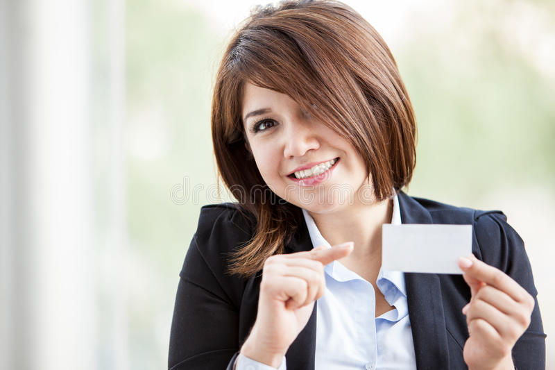 This is my business card. Happy young businesswoman holding a business card in one hand and pointing at it with the other stock image