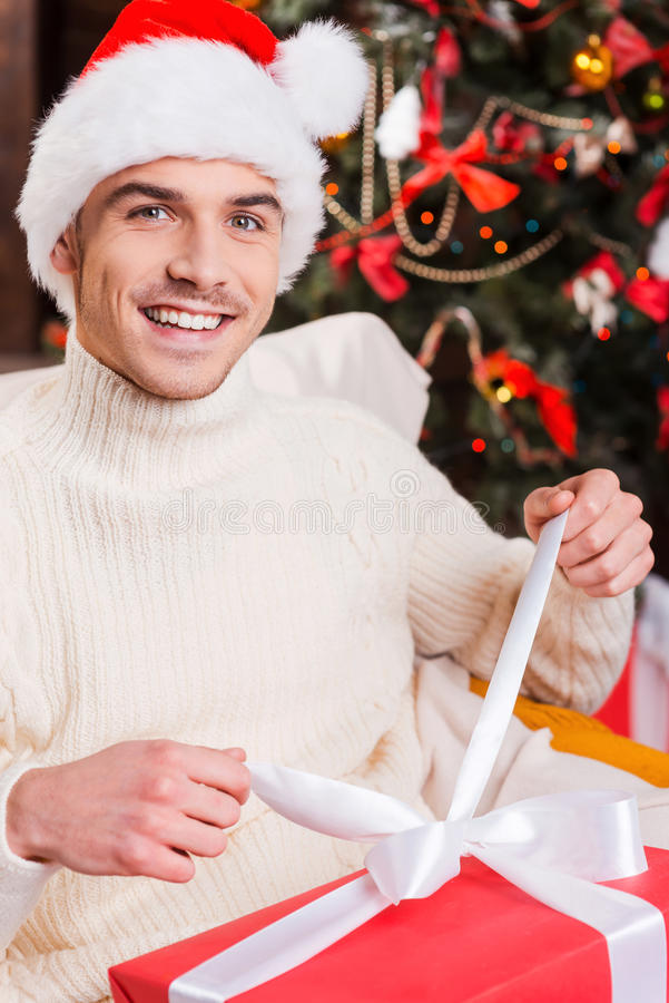 My Christmas present. Handsome young man in Santa hat opening gift box and smiling with Christmas Tree in the background royalty free stock photo