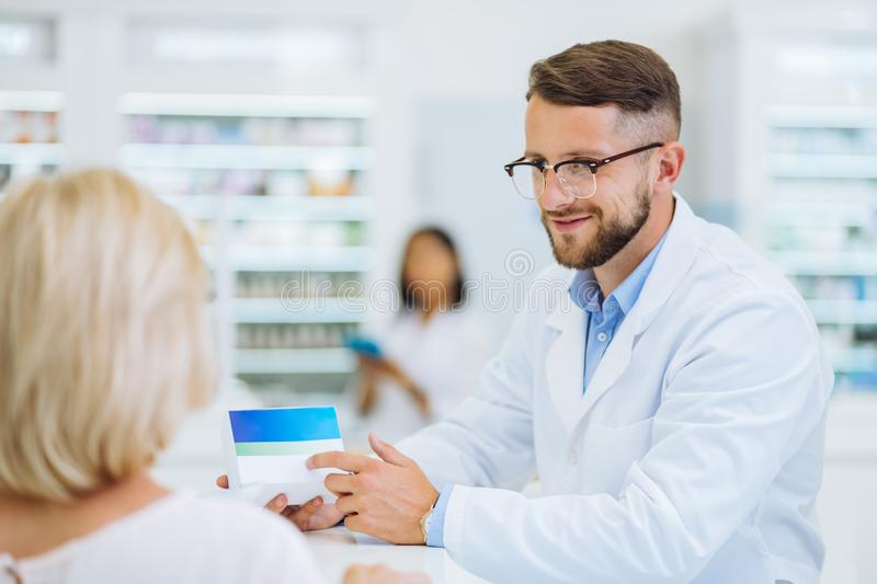 Cheerful young male person pointing at pills stock photo