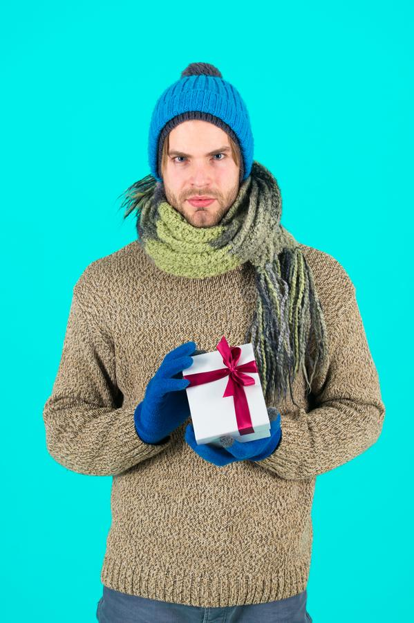My congratulations. Man bearded handsome wear winter hat scarf gloves hold gift box. Hipster hold christmas gift with royalty free stock photo