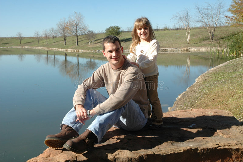 My Dad. A dad sits on a rock by a pond as his daughter comes up behind him. Father and daughter at the park stock images