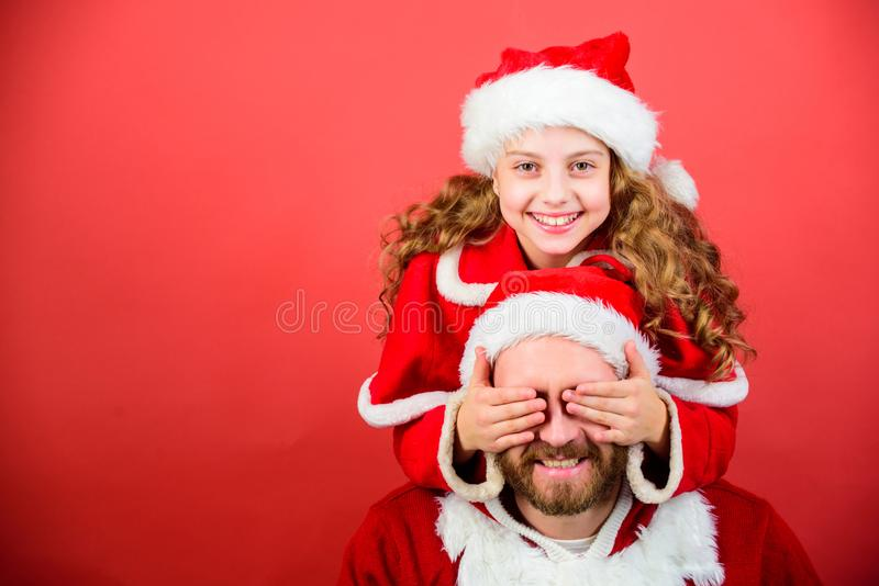 My dad is santa claus. Belief in santa constitutes most magical part of childhood. Guess who. Surprise concept. Girl. Child and bearded father wear santa stock images