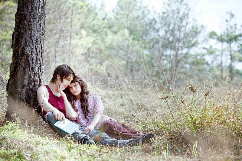 My Dreaming Love. Girl in flowery pink peasant top leaning against sleeping boy in red tank top holding a book of love poems in romantic outdoor image royalty free stock image