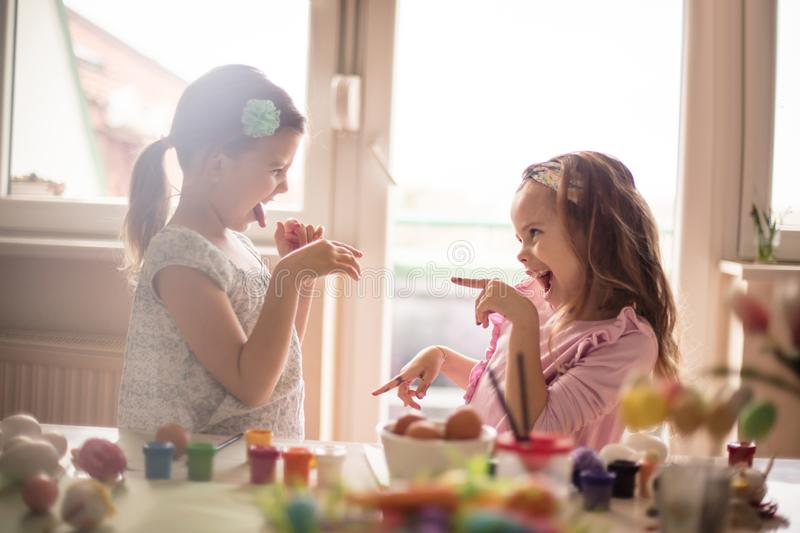 My Easter decorations are better than yours. Little girls coloring Easter egg royalty free stock photo