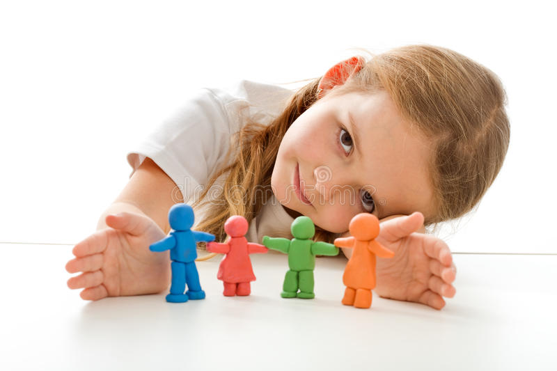 My family is safe. Insurance concept with little girl shielding clay people stock image