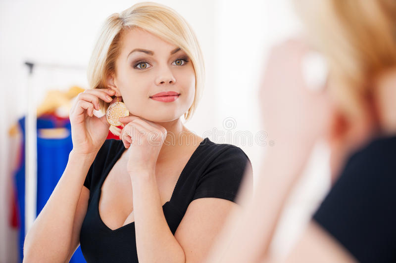 My favorite earrings!. Beautiful young blond hair woman wearing earrings and smiling while looking at the mirror royalty free stock photo