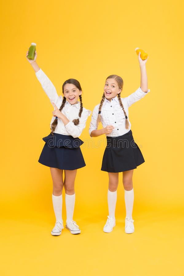 My favourite food. happy classmates in school uniform. back to school. little girls hold healthy juice or yoghurt. lunch royalty free stock images
