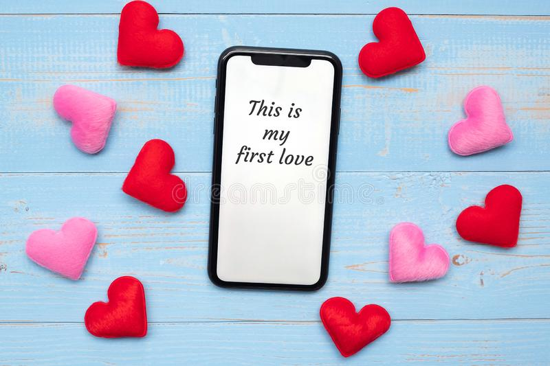 THIS IS MY FIRST LOVE word on white touchscreen display of black smart phone with red and pink hearts shape decoration on blue stock images