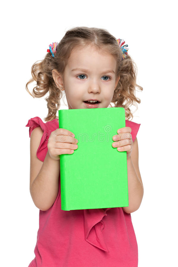 My frst book!. A cheerful preschool girl with a book against the white background stock photos